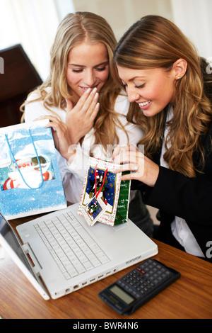 Girls in office opening secret Santa presents - Stock Photo