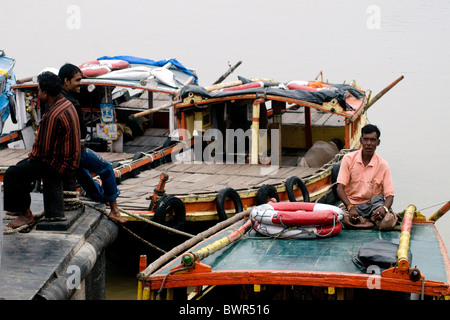 A boatman relaxes atop a ferryboat on the Hooghly river on the Howrah shore near Kolkata - Stock Photo