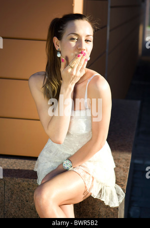 confused girl sits near wall of building and sends air kiss - Stock Photo