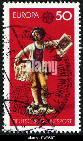 GERMANY- CIRCA 1976: A stamp printed in Germany, shows Postman, circa 1976 - Stock Photo