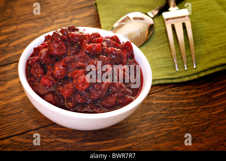 Bowl of fresh homemade cranberry sauce on antique oak table - Stock Photo