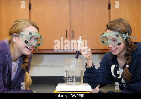 Students wearing splash-proof safety goggle while doing a science experiment - Stock Photo