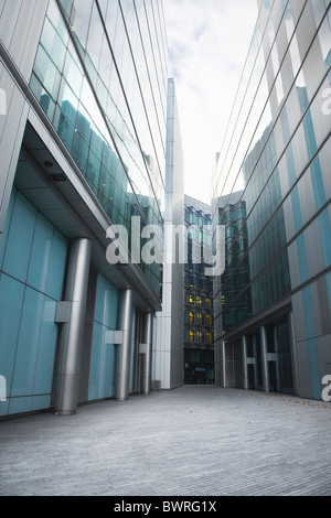 Glass office buildings and building on More London Place with office lights on in the background - Stock Photo