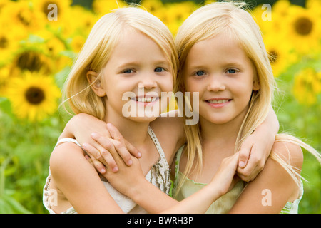 Portrait of cute twins embracing each other on background of sunflower field - Stock Photo