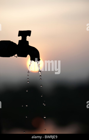 Silhouette of a stand pipe tap at sunrise with dripping water - Stock Photo