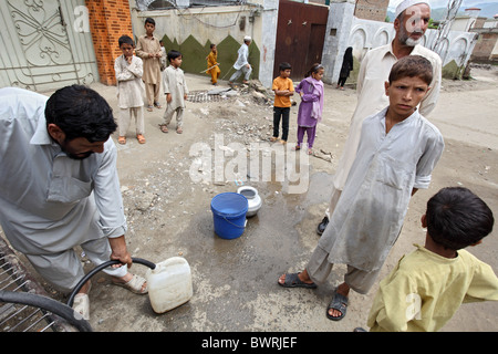 Mobile drinking water distribution by Handicap International, Mingora, Pakistan - Stock Photo