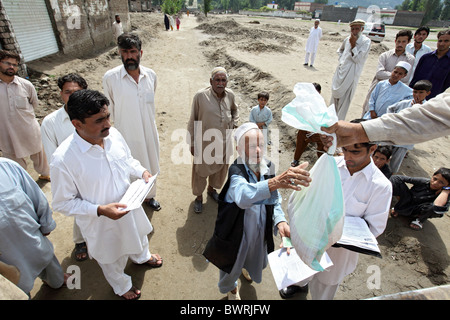 Distribution of relief goods by Handicap International, Mingora, Pakistan - Stock Photo