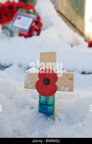 Poppies laid at a war memorial in the snow - Stock Photo