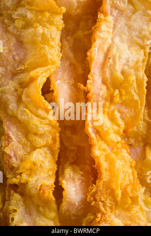 Chicken-Fried Bacon - Bacon slices dipped in a batter of whole dry milk and water, tossed in flour and deep fried. - Stock Photo