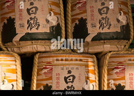Ceremonial stacked sake barrels at a Japanese temple covered in pictures and writing