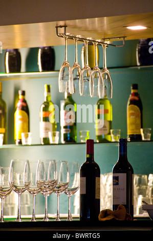Liquor bottles and wine glasses sitting on bar counter in restaurant - Stock Photo