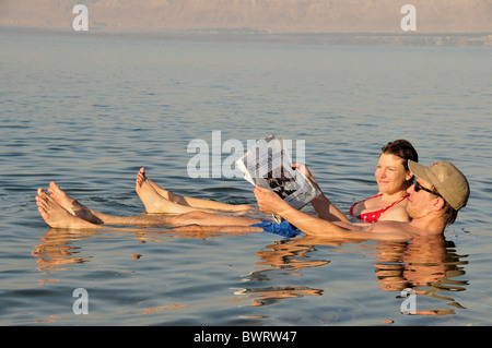 Tourists reading the newspaper in the Dead Sea near Suwaymah, Jordan, Middle East, Orient - Stock Photo