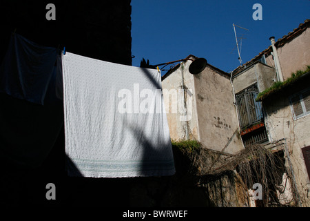 bed sheets on washing line outdoors in sun in italy - Stock Photo