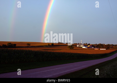 A double rainbow has formed over a small valley on the plains of Illinois after a thunderstorm has passed. - Stock Photo