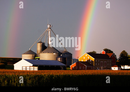 A double rainbow glows over a small farm in Illinois after a thunderstorm has just passed. - Stock Photo