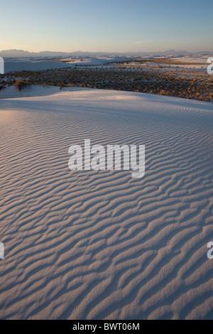 Warm sunset light falls across the white gypsum sand dunes of White Sands National Monument in Alamogordo, New Mexico, - Stock Photo