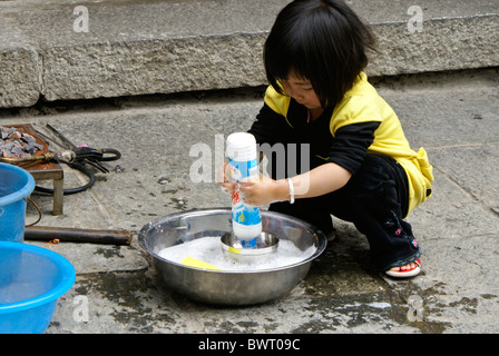 Little girl playing in water, Dali, Yunnan, China - Stock Photo