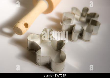 close up of Christmas cookie cutter shapes and handle of wooden rolling pin - Stock Photo