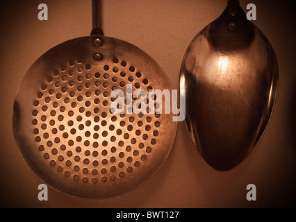 Kitchen utensils hanging on wall. Spoon and draining spoon. - Stock Photo