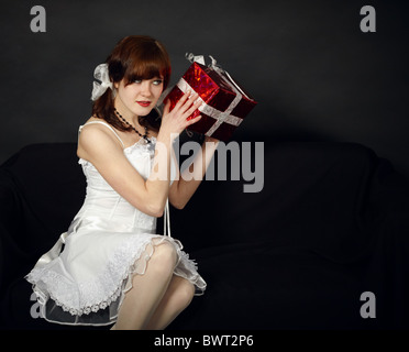 The happy young girl has received a gift on dark background - Stock Photo