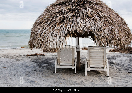 Two plastic chaise lounge chairs under a palapa structure offer shade and privacy on Panama's Playa Blanca. - Stock Photo