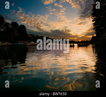 Two anglers in an inflatable boat while the dawn light is reflected in the River Thames below the weir at Teddington - Stock Photo