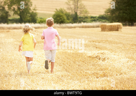 Children Running Through Summer Harvested Field - Stock Photo