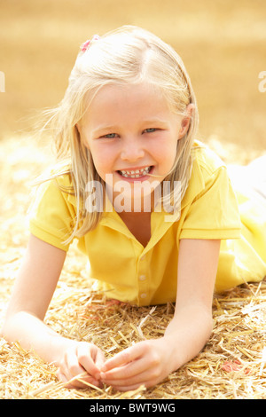 Portrait Of Girl Laying In Summer Harvested Field - Stock Photo