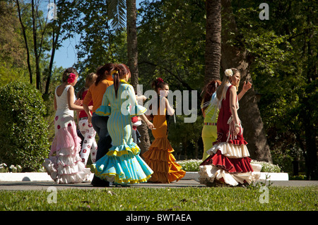Women in flamenco dress walking through Maria Luisa Park towards the Seville Spring Fair, Seville, Andalusia, Spain. - Stock Photo