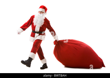 Portrait of Santa Claus carrying heavy sack with presents - Stock Photo