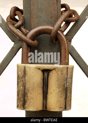 The old padlock and rusty chain on a metal lattice. - Stock Photo