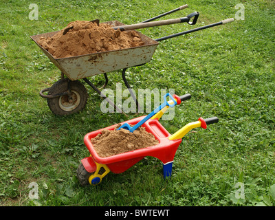 Two wheelbarrows with sand on green to a grass. - Stock Photo