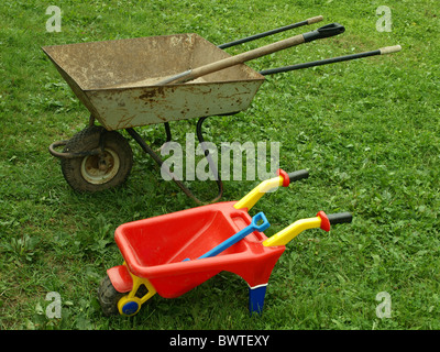 Two wheelbarrows on green to a grass. - Stock Photo