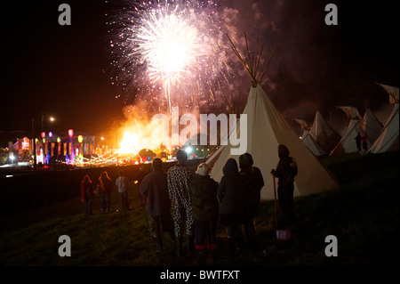 Spectators gather to watch fireworks burst above the main stage at the conclusion of Bestival 2010 in Newport, Isle - Stock Photo