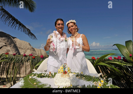 Newlyweds holding glasses of champagne in La Digue, Seychelles - Stock Photo
