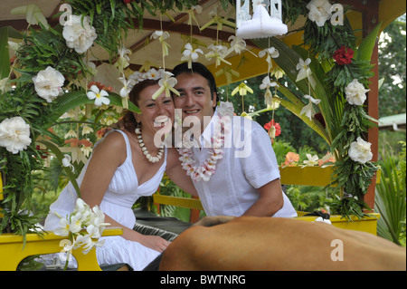 Newlyweds sitting on a decorated oxcart in La Digue, Seychelles - Stock Photo