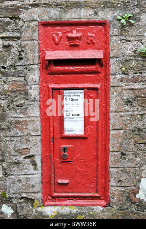 Victorian British red postbox in a stone wall in Dartmouth, Devon - Stock Photo