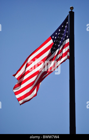 American flag blowing against blue sky - Stock Photo