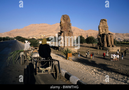 Tourists visiting Colossi of Memnon, two massive stone statues of Pharaoh Amenhotep III, in the Theban necropolis, - Stock Photo