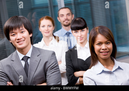 Photo of successful business partners looking at camera with other specialists behind them - Stock Photo