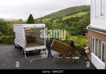 Two men removing furniture from a rural house for a community recycling project in Newtown Powys Mid Wales UK - Stock Photo