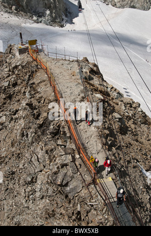 Climbers return to Helbronner Cable car station French Italian border. - Stock Photo