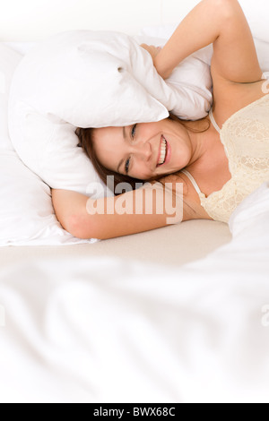 Bedroom - lazy woman getting up blocking ears - Stock Photo