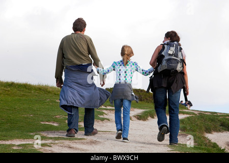 Parents and their young daughter walking arm in arm along the Dorset coast path from Durdle Door to Lulworth Cove. - Stock Photo