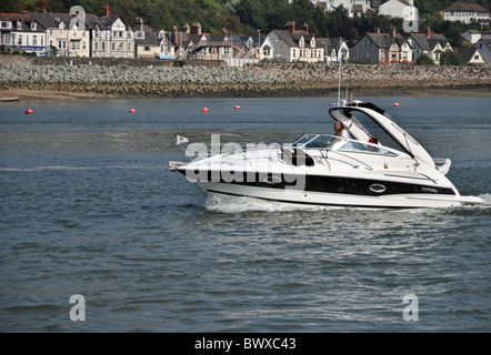 A motor boat sailing down the River Conwy   (Afon Conwy) in North Wales. - Stock Photo