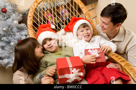 Portrait of happy kids in Santa caps surrounded by their parents - Stock Photo