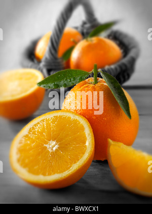 Fresh oranges whole and cut halves with leaves in a kitchen setting - Stock Photo