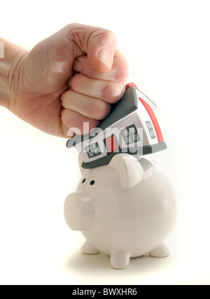 HOUSE HIT AND SQUASHED BY MANS HAND ON PIGGY BANK RE SAVINGS HOUSING MARKET MORTGAGES HOUSE PRICES ETC UK - Stock Photo