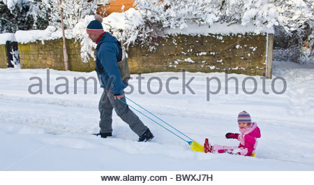 Man pulling little girl on a yellow sledge through a snow covered street and both wearing winter clothing. - Stock Photo