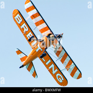 Single Breitling Boeing Stearman biplane at Eastbourne Airbourne Air Display with a wingwalker on top wing - plane - Stock Photo